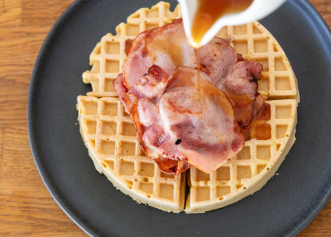 Gluten free lupin waffles topped with bacon and maple syrup