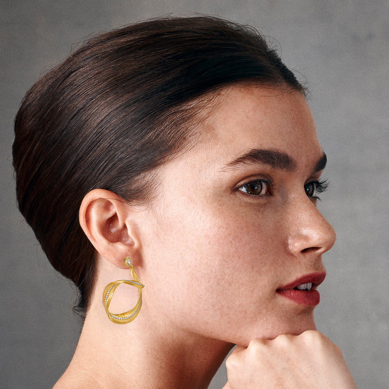 Model showing a yellow gold earring take the form of a delicate eucalyptus leaf