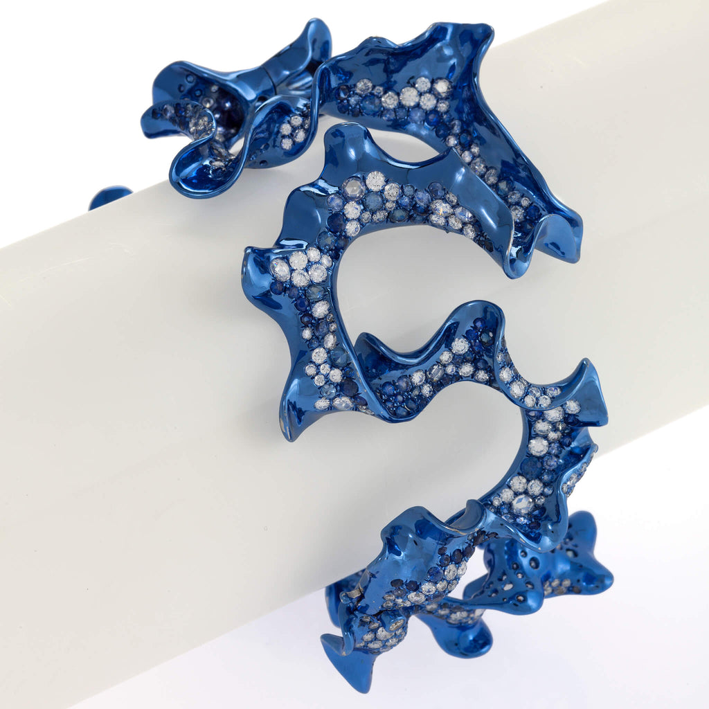 Swirling blue rhodium plated cuff with diamonds and sapphires by Neha Dani available at Macklowe Gallery