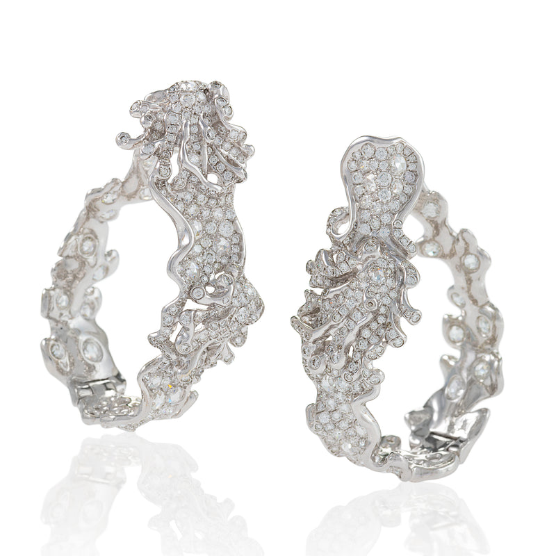 Compressed hoop earrings featuring round full and rose cut diamonds arranged in swirling motifs by neha dani