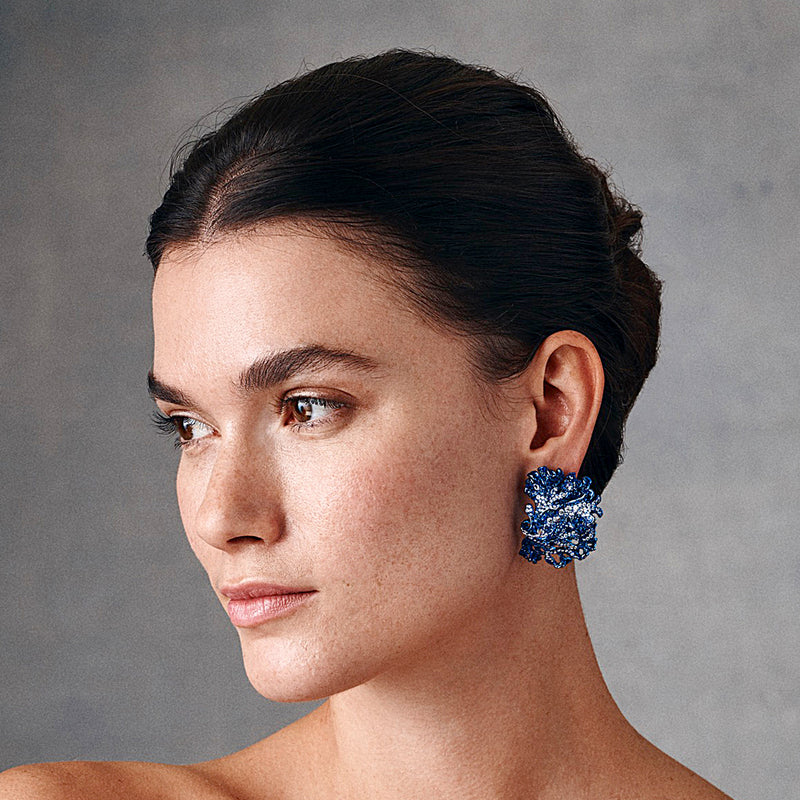 Model showing blue rhodium plated underwater bloom ear clips