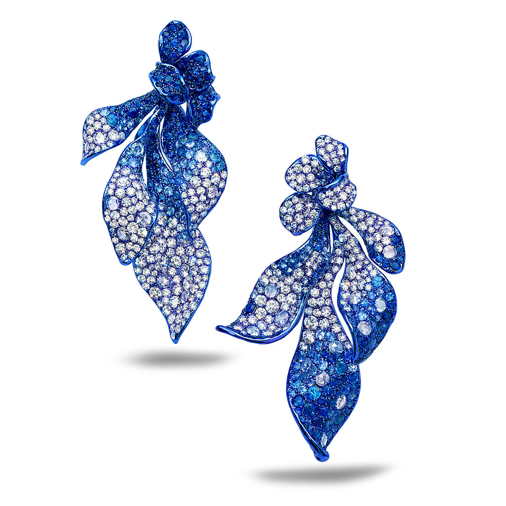Drop earrings that have a delicate top of four floral petals, and a drop of four unique, elongated dancing petals in graduating tones of VVS clarity, E/F color diamonds and sapphires by Neha Dani available at Macklowe Gallery