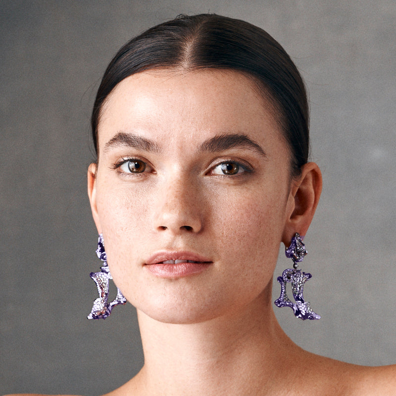 Model showing a pair of purple rhodium plated and diamond studded earrings