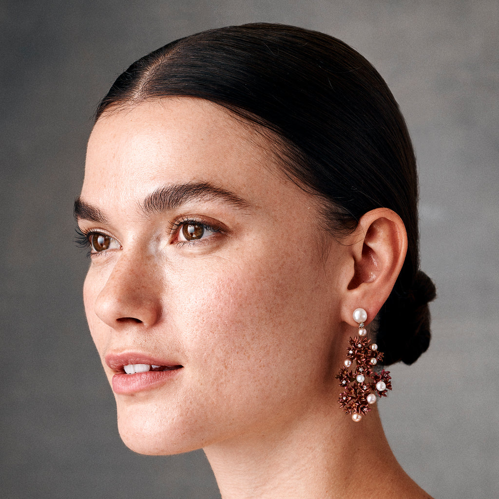Model showing Titanium bronze-colored earrings with pearls