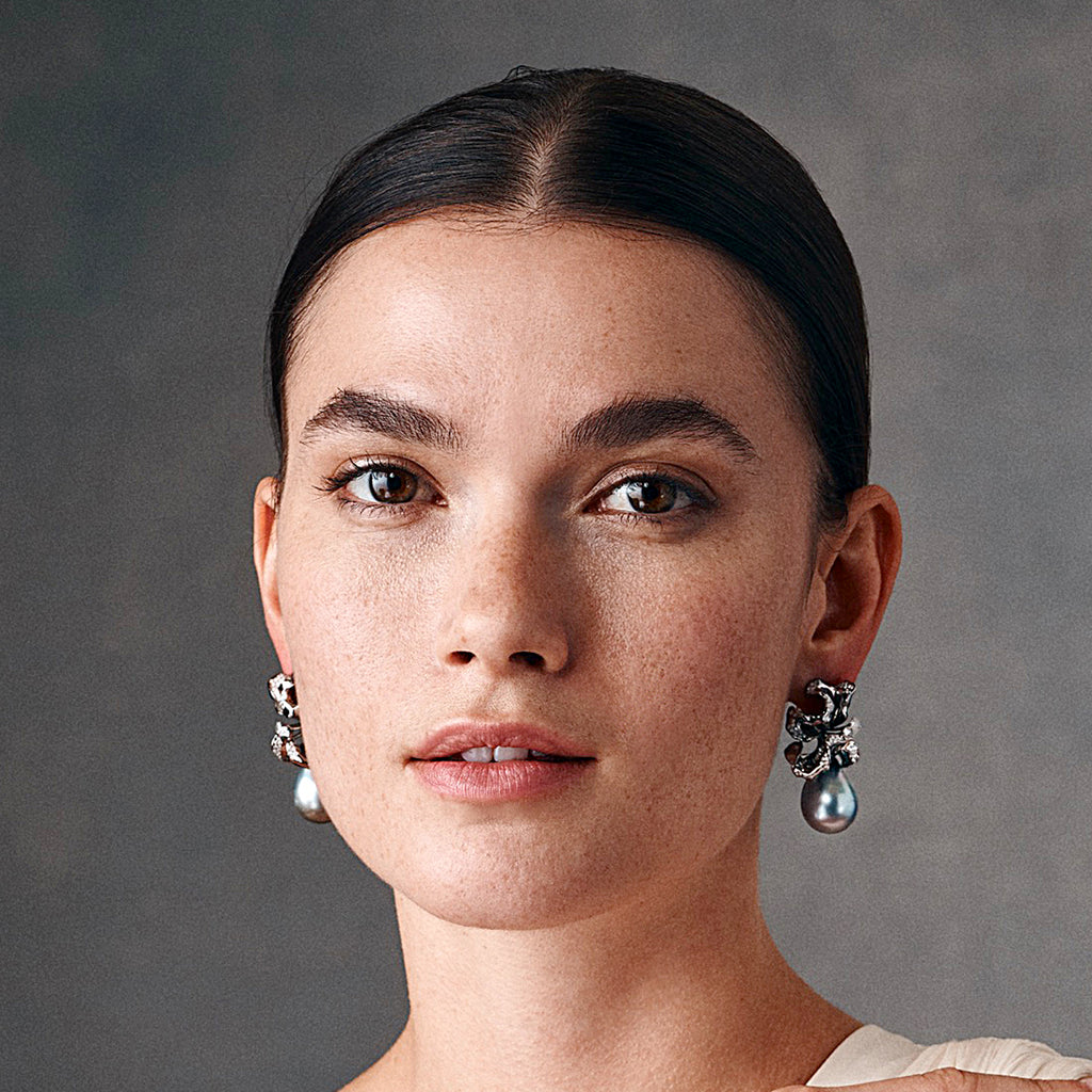 Model showing diamond studded white gold and Tahitian pearl earrings