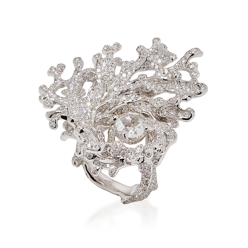 18 karat white gold ring centers on a rose cut diamond of 0.32 carat, surrounded by white gold and diamonds that charge dramatically outward in a circular motif that mimics the energetic movement of a maelstrom by Neha Dani available at Macklowe Gallery