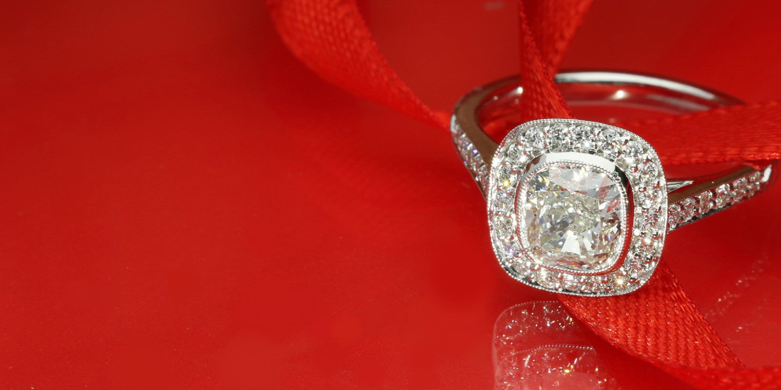 Cushion cut diamond halo engagement ring on a red ribbon background