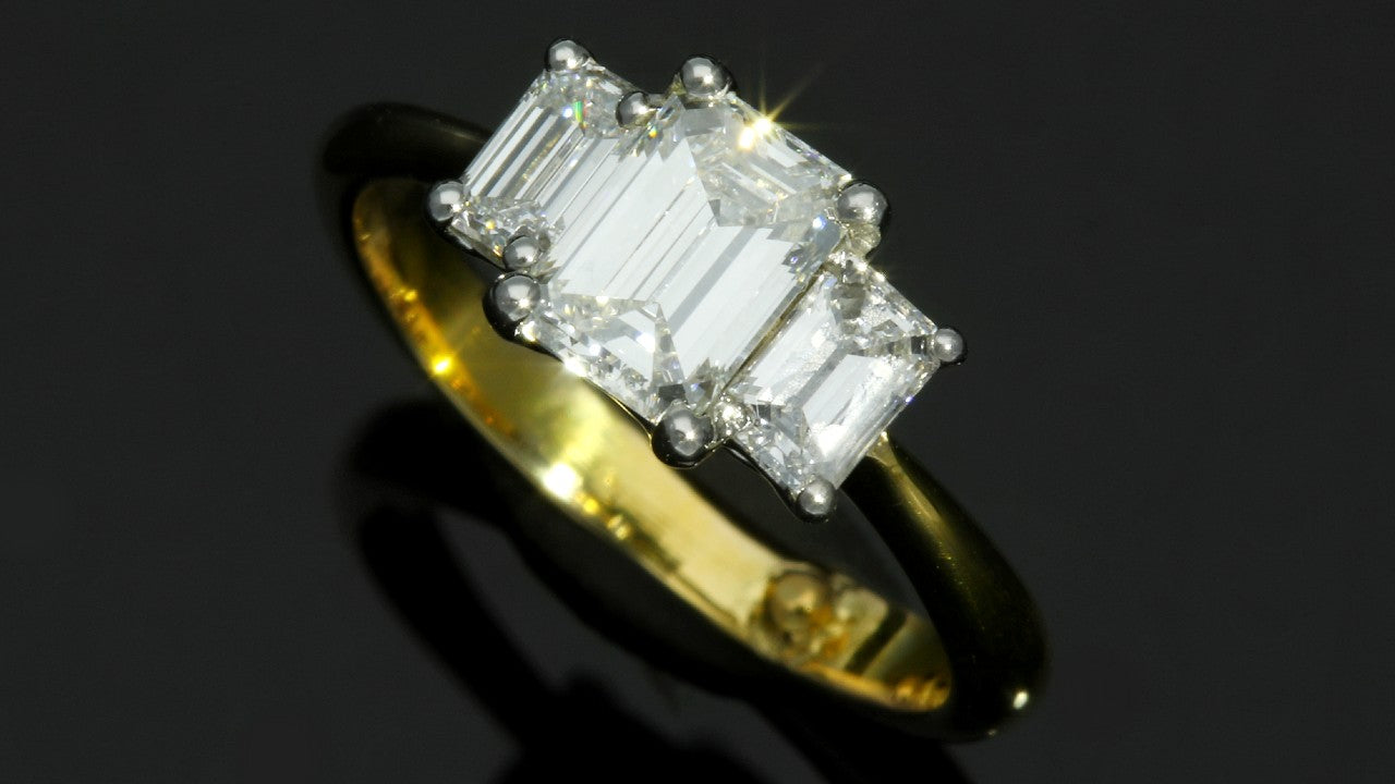 Three stone emerald cut diamond engagement ring yellow gold
