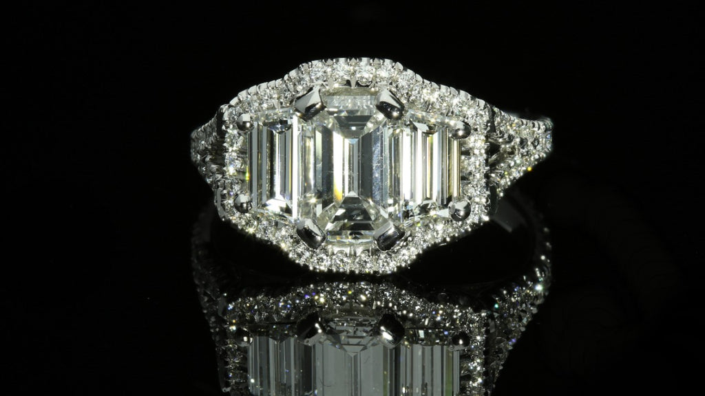 Three stone emerald cut halo engagement ring