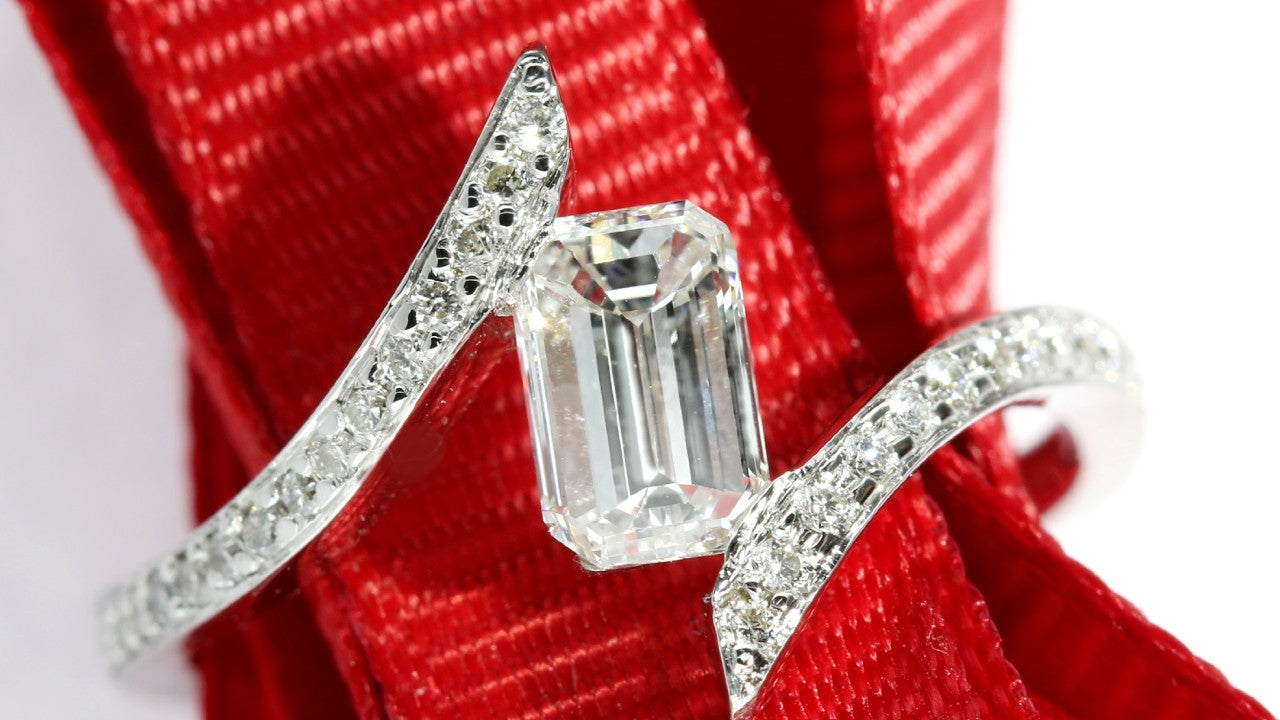 Tension set pave engagement ring set with an emerald cut center diamond