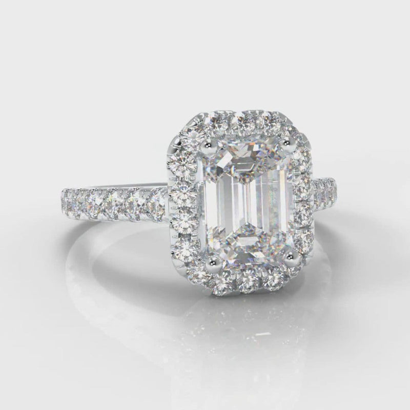 Halo engagement ring set with an emerald cut diamond centre stone, encircled by a glistening diamond halo