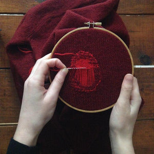 red sweater being mended with red thread