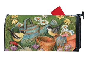 MailWrap with a goldfinch and chickadee sitting on garden tools next to a pair of garden gloves, pack of flower seeds, a watering can and two empty clay flower pots surrounded by wildflowers