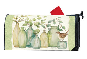 MailWrap with 6 different shaped vases full of eucalyptus branches and one little brown bird atop the smallest vase