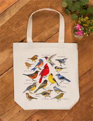 Bird Study Cotton Tote Bag with a variety of colorful birds illustrated on front laying on a tabletop
