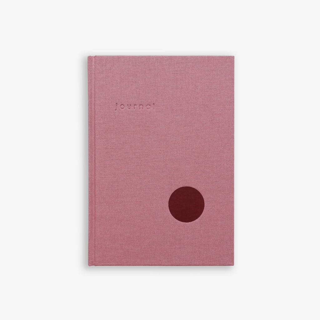 Rose pink hardcover fabric journal with embossed lettering saying 'Journal' and a circular detail