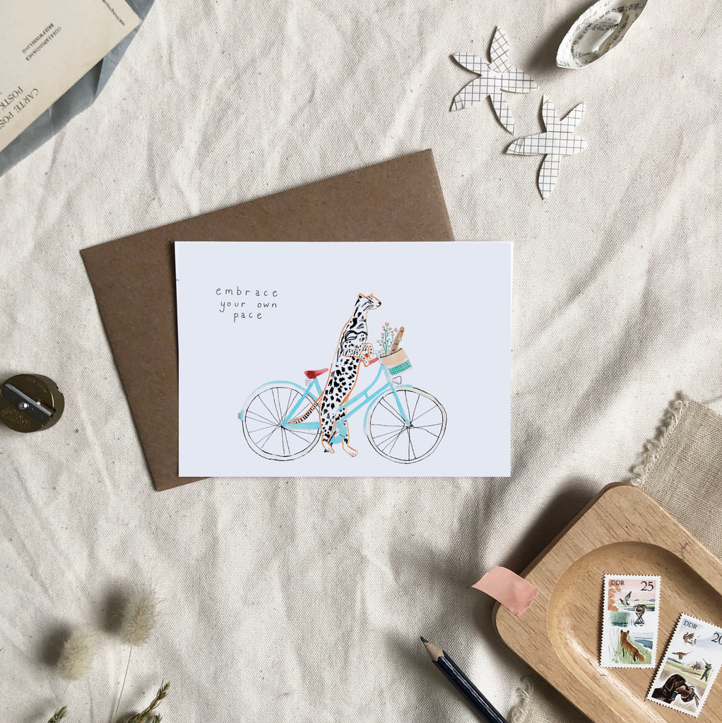 A greetings card saying 'embrace your own pace' with a painted animal riding a bike on it