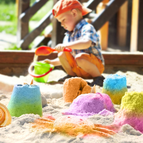 child in sandbox with colored sandcastles