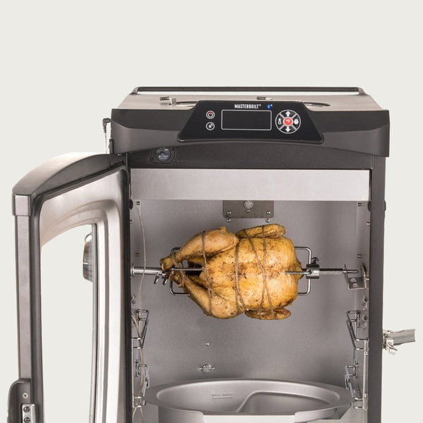 Chicken on rotisserie spit with meat hooks installed inside smoker cabinet