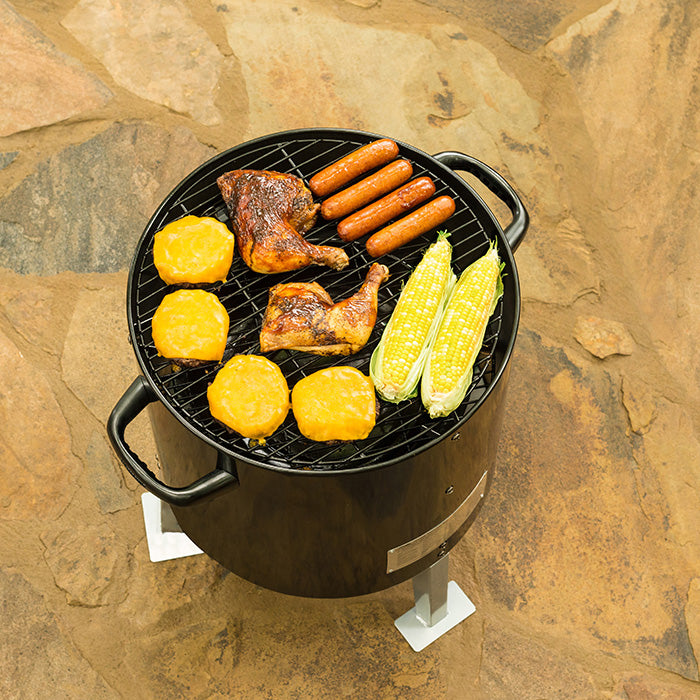 Charcoal Bullet Smoker ready to go with hot dogs, chicken quarters and vegetables. Dinner for the whole family.