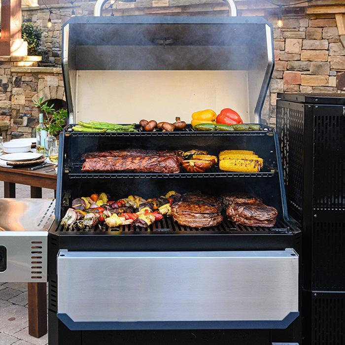 Masterbuilt Gravity Series 1050 Grill + Smoker filled with grilled food