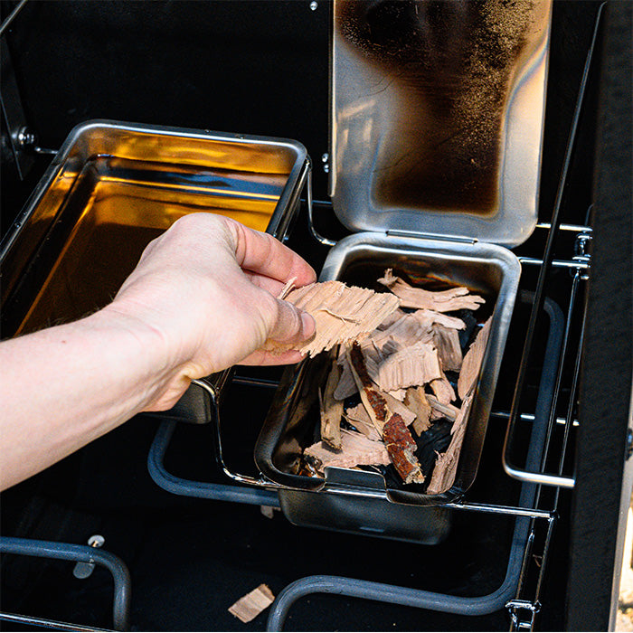 Adding chips to the chip tray of the Analog Electric Smoker