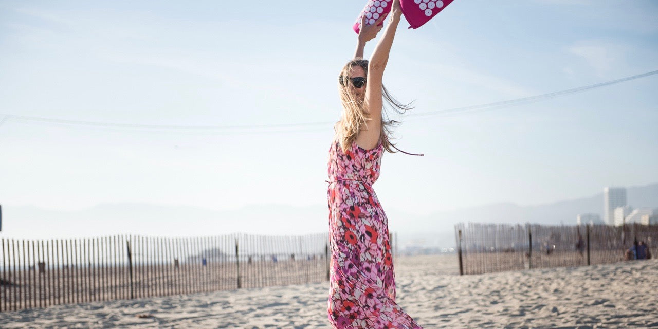 Woman on beach wearing long pink floral dress holding a pink Bed of Nails Acupressure Mat and Pillow