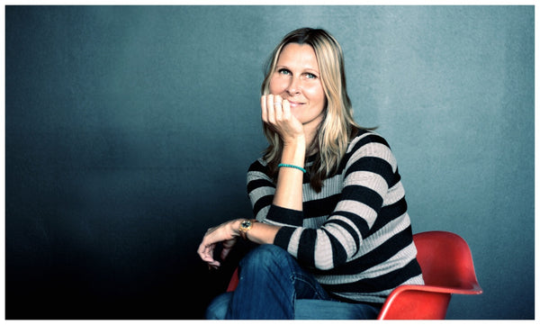 Blonde woman wearing black and white striped shirt and jeans, sitting on a red chair against a blue background