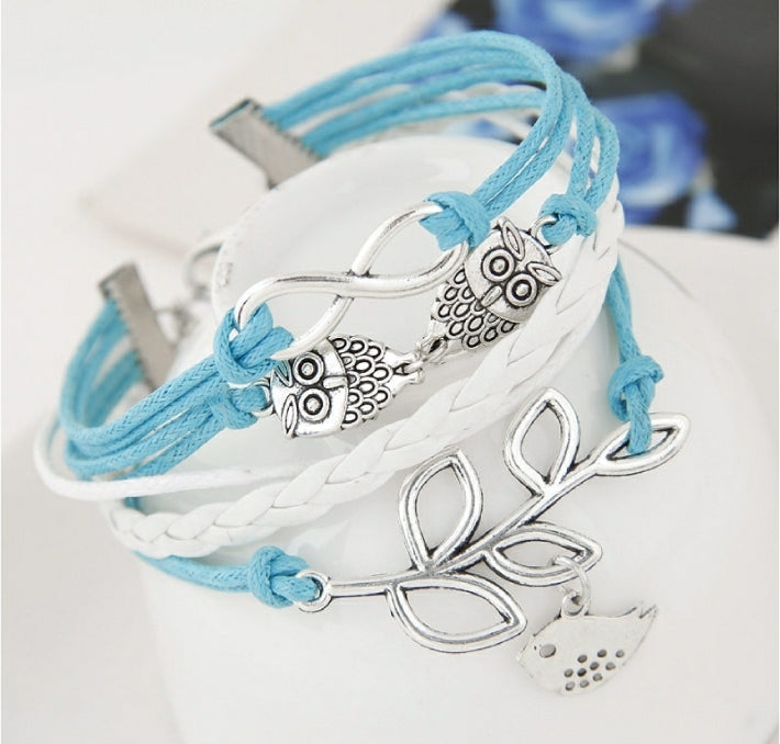 BLUE AND WHITE 5 BRACELET STACK WITH BIRD ON A BRANCH, OWL, AND INFINITY CHARMS IN SILVER