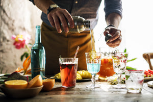 bartender wearing a brown apron pouring from a cocktail shaker into a cocktail glass on a table with cocktails and fresh fruit