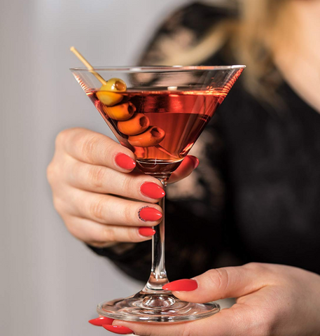 A woman with bright red nails holding a martini glass with a red cocktail and 3 olives