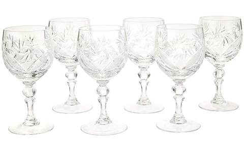 6 old fashioned wine glasses in a staggered line against a white background