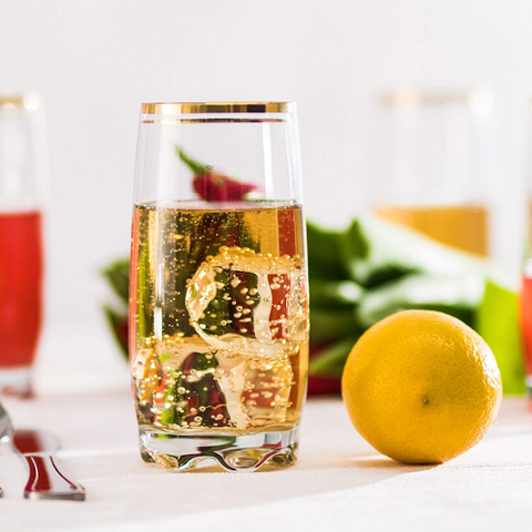 a highball glass containing a bubbly gold liquid and ice next to a fresh whole lemon