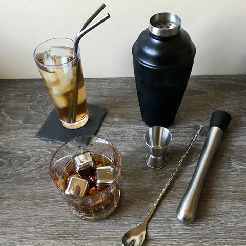 A range of barware for bartenders including a black cocktail shaker, jigger, muddle, spoon and a glass with stainless steel straws and whiskey rocks