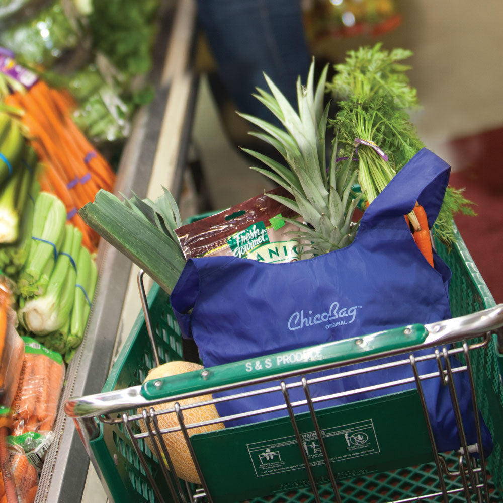 ChicoBag Mazarine Blue original Bag with produce inside in a grocery store