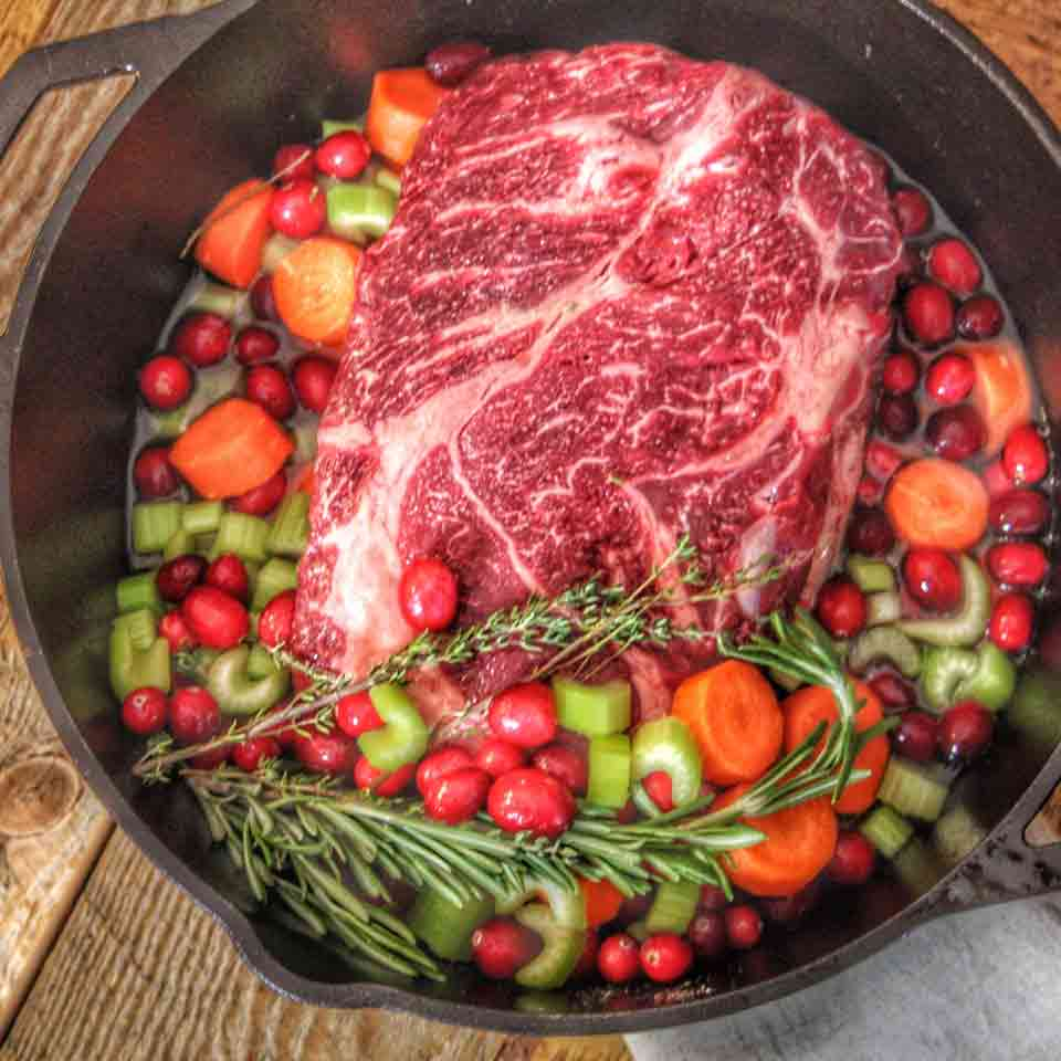 Cranberry Pot Roast, uncooked, in a dutch oven.