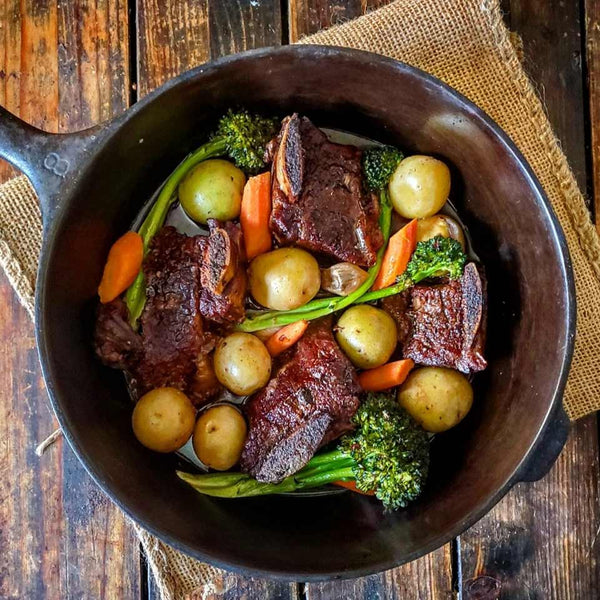 Braised short ribs recipe shown in a cast iron skillet