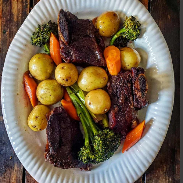 braised short ribs recipe displayed with potatoes, carrots and broccoli on a white plate