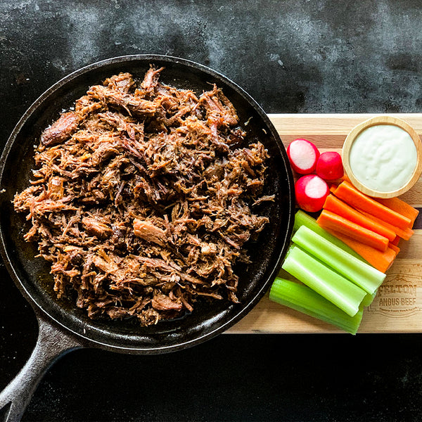 A pan of buffalo shredded beef beside carrots, celery, radishes and dip.