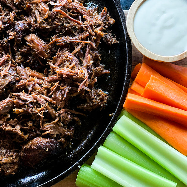 a close up image of shredded beef with buffalo sauce