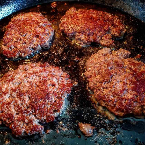 Smash burgers frying in a cast iron skillet