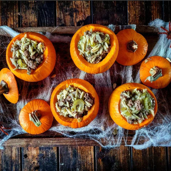 Image of green chili stew inside small pumpkins for Halloween
