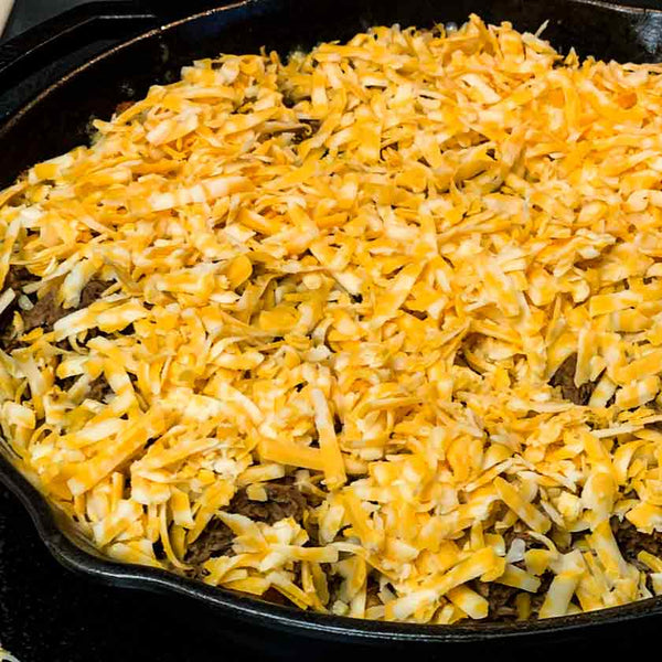 Tater tot nachos covered in shredded cheese