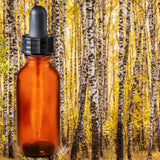 Essential Oil | Birch | The background is a wood full of tall, thin birch trees trunks in autumn. A glass amber dropper bottle is in the foreground.