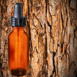 Essential Oil | Cedarwood | The background is the bark of a cedar tree. A glass amber dropper bottle is in the foreground.