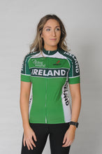 Load image into Gallery viewer, A woman wears the Team Ireland Short Sleeved cycling jersey which is green with white panels and sports the Spin 11 and Cycling Ireland logos