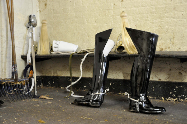 Ross Watson photograph of queens guard boots, helmut and sword discarded in stables