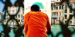 Ross Watson triptych photograph of orange robed monk with lattice obscured views of venice either side