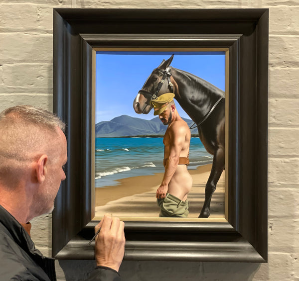 Ross Watson signing an original oil painting in a heavy black italianate frame of a partially dressed soldier with a horse on a beach