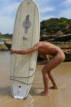 Ross Watson photograph of naked surfer on beach bending over with his head behind an upright white surfboard